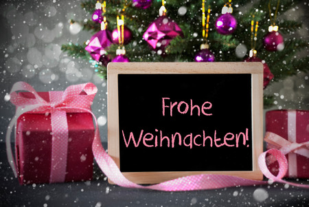 weihnachten: Chalkboard With German Text Frohe Weihnachten Means Merry Christmas. Christmas Tree With Rose Quartz Balls, Snowflakes And Bokeh Effect. Gifts Or Presents In The Front Of Cement Background.