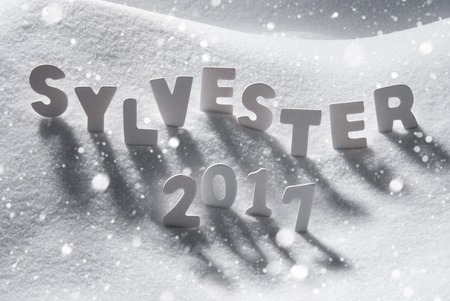 sylvester: White Letters Building German Text Sylvester 2017 Means New Years Eve 2017 In Snow. Snowy Scenery With Snowflakes For Happy New Year Greetings.