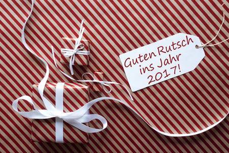 ins: Two Gifts Or Presents With White Ribbon. Red And Brown Striped Wrapping Paper. Christmas Or Greeting Card. Label With German Text Guten Rutsch Ins Jahr 2017 Means Happy New Year
