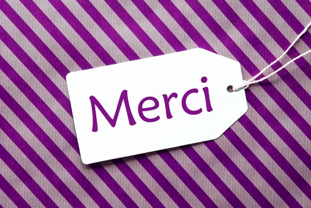 merci: One Label On A Purple Striped Wrapping Paper. Textured Background. Tag With Ribbon. French Text Merci Means Thank You Stock Photo