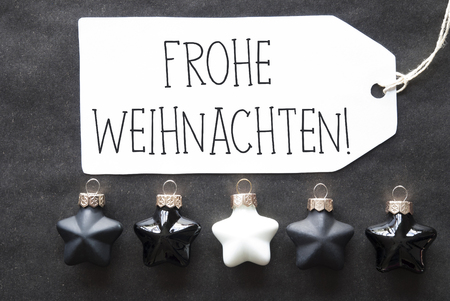christmas ornamentation: Label With German Text Frohe Weihnachten Means Merry Christmas. Black And White Christmas Tree Balls On Black Paper Background. Christmas Decoration Or Texture. Flat Lay View