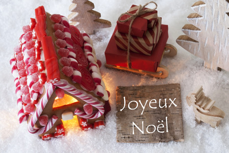 joyeux: Label With French Text Joyeux Noel Means Merry Christmas. Gingerbread House On Snow With Christmas Decoration Like Trees And Moose. Sleigh With Christmas Gifts Or Presents. Stock Photo
