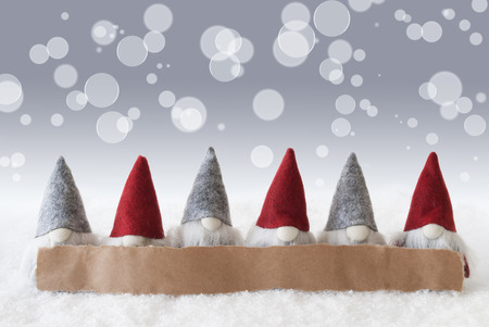 Label With Copy Space For Advertisement. Christmas Greeting Card With Gnomes. Sparkling Bokeh And Silver Background With Snow