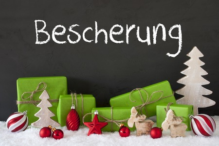 German Text Bescherung Means Gift Giving. Green Gifts Or Presents With Christmas Decoration Like Tree, Moose Or Red Christmas Tree Ball. Black Cement Wall As Background With Snow.