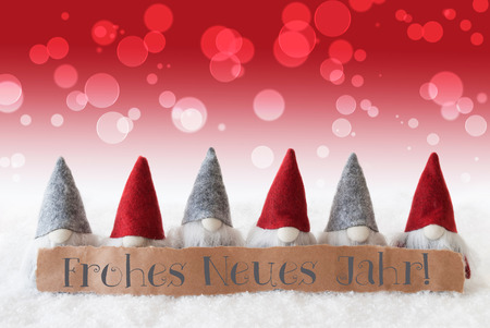 jahr: Label With German Text Frohes Neues Jahr Means Happy New Year. Christmas Greeting Card With Red Gnomes. Bokeh And Christmassy Background With Snow. Stock Photo