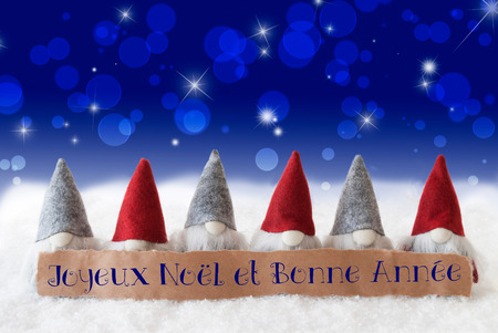 Label With French Text Joyeux Noel Et Bonne Annee Means Merry Christmas And Happy New Year. Christmas Greeting Card With Gnomes. Sparkling Bokeh And Blue Background With Snow And Stars.