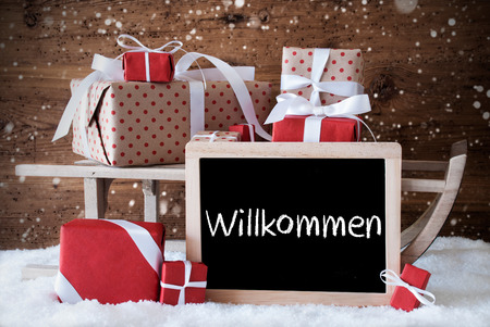 willkommen: Chalkboard With German Text Willkommen Means Welcome. Sled With Christmas And Winter Decoration And Snowflakes. Gifts And Presents On Snow With Wooden Background.
