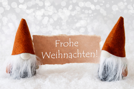 frohe: Christmas Greeting Card With Two Bronze Gnomes. Sparkling Bokeh Background With Snow. German Text Frohe Weihnachten Means Merry Christmas