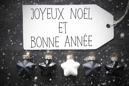 bonne: Label With French Text Joyeux Noel Et Bonne Annee Means Merry Christmas And Happy New Year. Black And White Christmas Tree Balls On Black Paper Background With Snowflakes. Flat Lay View