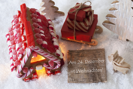 Label With German Text Am 24. Dezember Ist Weihnachten Means December 24th Is Christmas Eve. Gingerbread House On Snow With Christmas Decoration Like Trees And Moose. Sleigh With Christmas Gifts.
