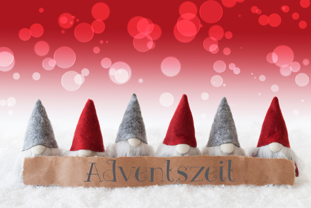 advent season: Label With German Text Adventszeit Means Advent Season. Christmas Greeting Card With Red Gnomes. Bokeh And Christmassy Background With Snow.