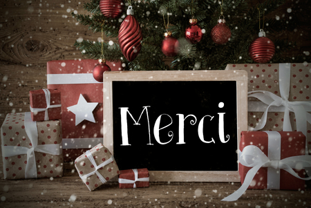 nostalgic christmas: Nostalgic Christmas Card For Seasons Greetings. Christmas Tree With Balls And Snowflakes. Gifts Or Presents In The Front Of Wooden Background. Chalkboard With French Text Merci Means Thank You Stock Photo