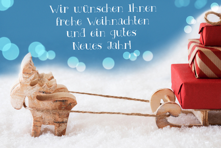 German Text Frohe Weihnachten Und Ein Gutes Neues Jahr Means Merry Christmas And Happy New Year. Moose Is Drawing A Sled With Red Gifts Or Presents In Snow. Light Blue Background With Bokeh Effect. Stock Photo