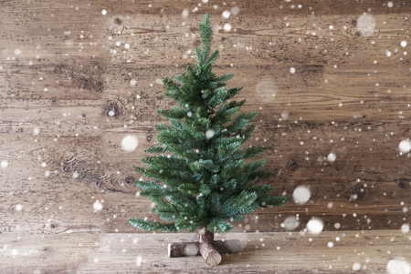 Christmas Card For Seasons Greetings And Snowflakes. Green Christmas Tree With In The Front Of Aged Wooden Background. Rustic Or Retro Style. Copy Space For Advertisement Stock Photo
