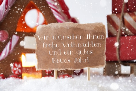 weihnachten: Gingerbread House In Snowy Scenery As Christmas Decoration. Sleigh With Gifts And Snowflakes. Label With German Text Frohe Weihnachten Und Ein Gutes Neues Jahr Means Merry Christmas And Happy New Year