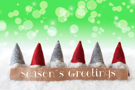 Label With English Text Seasons Greetings. Christmas Greeting Card With Gnomes. Sparkling Bokeh And Green Background With Snow And Stars.