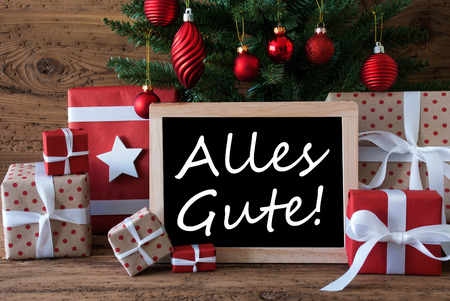 christmas tree presents: Colorful Christmas Card For Seasons Greetings. Christmas Tree With Red Balls. Gifts Or Presents In The Front Of Wooden Background. Chalkboard With German Text Alles Gute Means Best Wishes Stock Photo