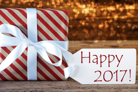 atmospheric: Macro Of Christmas Gift Or Present On Atmospheric Wooden Background. Card For Seasons Greetings, Best Wishes Or Congratulations. White Ribbon With Bow. English Text Happy 2017 Stock Photo