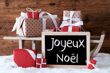 Chalkboard With French Text Joyeux Noel Means Merry Christmas. Sled With Christmas And Winter Decoration. Gifts And Presents On Snow With Wooden Background.