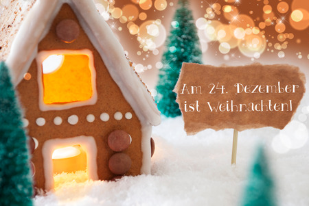 weihnachten: Gingerbread House In Snowy Scenery As Christmas Decoration. Christmas Trees And Candlelight. Bronze And Orange Background With Bokeh Effect. German Text Am 24. Dezember Ist Weihnachten Means Christmas