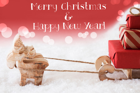 christmassy: Moose Is Drawing A Sled With Red Gifts Or Presents In Snow. Christmas Card For Seasons Greetings. Red Christmassy Background With Bokeh Effect. English Text Merry Christmas And Happy New Year