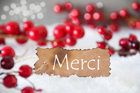 Burnt Label With French Text Merci Means Thank You. Red Christmas Decoration On Snow. Cement Wall As Background With Bokeh Effect. Card For Seasons Greetings