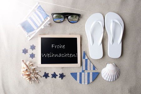 weihnachten: Flat Lay Of Chalkboard On Sandy Background. Sunny Summer Decoration As Holiday Greeting Card. Sand And Beach Environment. German Text Frohe Weihnachten Means Merry Christmas