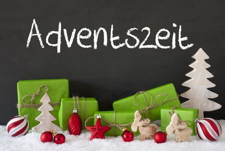 German Text Adventszeit Means Advent Season. Green Gifts Or Presents With Christmas Decoration Like Tree, Moose Or Red Christmas Tree Ball. Black Cement Wall As Background With Snow. Stock Photo