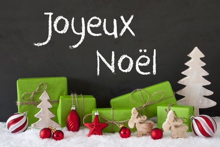 joyeux: French Text Joyeux Noel Means Merry Christmas. Green Gifts Or Presents With Christmas Decoration Like Tree, Moose Or Red Christmas Tree Ball. Black Cement Wall As Background With Snow.