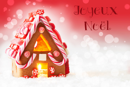 joyeux: Gingerbread House In Snowy Scenery As Christmas Decoration. Candlelight For Romantic Atmosphere. Red Background With Bokeh Effect. French Text Joyeux Noel Means Merry Christmas