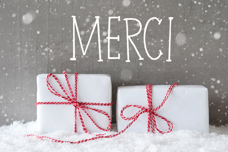 merci: French Text Merci Means Thank You. Two White Christmas Gifts Or Presents On Snow. Cement Wall As Background With Snowflakes. Modern And Urban Style. Stock Photo