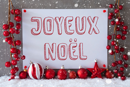 joyeux: Label With French Text Joyeux Noel Means Merry Christmas. Red Christmas Decoration Like Balls On Snow. Urban And Modern Cement Wall As Background With Snowflakes. Stock Photo