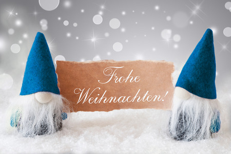 weihnachten: Christmas Greeting Card With Two Blue Gnomes. Sparkling Bokeh And Noble Silver Background With Snow. German Text Frohe Weihnachten Means Merry Christmas
