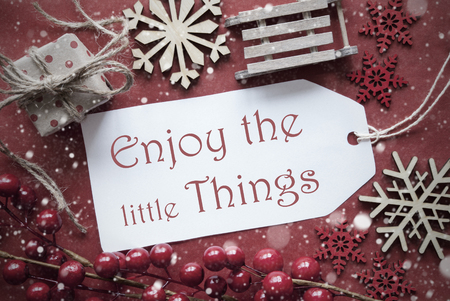 nostalgic christmas: Nostalgic Christmas Decoration Like Gift Or Present, Sleigh. Card For Seasons Greetings With Red Paper Background. English Quote Enjoy The Little Things