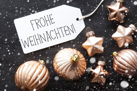 christmas ornamentation: Label With German Text Frohe Weihnachten Means Merry Christmas. Bronze Christmas Tree Balls On Black Paper Background With Snowflakes. Christmas Decoration Or Texture. Flat Lay View Stock Photo