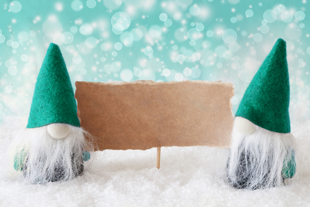 gnomos: Christmas Greeting Card With Two Turqoise Gnomes. Sparkling Bokeh Background With Snow. Copy Space For Advertisement Foto de archivo