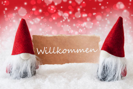 gnomos: Christmas Greeting Card With Two Red Gnomes. Sparkling Bokeh And Christmassy Background With Snow. German Text Willkommen Means Welcome