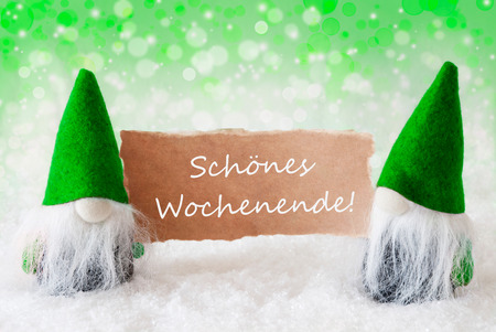 wochenende: Christmas Greeting Card With Two Green Gnomes. Sparkling Bokeh And Natural Background With Snow. German Text Schoenes Wochenende Means Happy Weekend