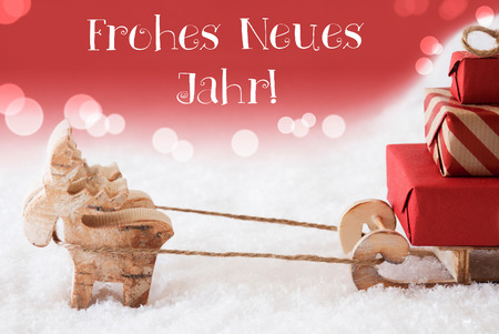 christmassy: Moose Is Drawing A Sled With Red Gifts Or Presents In Snow. Christmas Card For Seasons Greetings. Red Christmassy Background With Bokeh Effect. German Text Frohes Neues Jahr Means Happy New Year Stock Photo