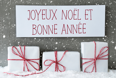 bonne: Label With French Text Joyeux Noel Et Bonne Annee Means Merry Christmas And Happy New Year. Three Christmas Gift Or Presents On Snow. Cement Wall As Background With Snowflakes. Modern And Urban Style. Stock Photo