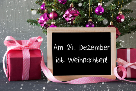 weihnachten: Chalkboard With German Text Am 24. Dezember Ist Weihnachten Means December 24th Is Christmas Eve. Christmas Tree With Rose Quartz Balls, Snowflakes.Gifts Or Presents In The Front Of Cement Background. Stock Photo