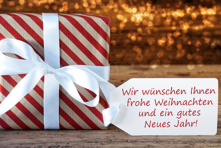 atmospheric: German Text Wir Wuenschen Ihnen Frohe Weihnachten Und Ein Gutes Neues Jahr Means Merry Christmas And Happy New Year. Macro Of Christmas Gift Or Present On Atmospheric Wooden Background.