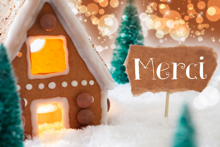 merci: Gingerbread House In Snowy Scenery As Christmas Decoration. Christmas Trees And Candlelight. Bronze And Orange Background With Bokeh Effect. French Text Merci Means Thank You