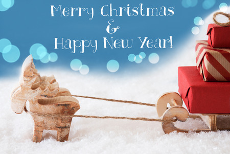 Moose Is Drawing A Sled With Red Gifts Or Presents In Snow. Christmas Card For Seasons Greetings. Light Blue Background With Bokeh Effect. English Text Merry Christmas And Happy New Year Stock Photo
