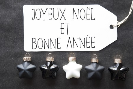 bonne: Label With French Text Joyeux Noel Et Bonne Annee Means Merry Christmas And Happy New Year. Black And White Christmas Tree Balls On Black Paper Background. Christmas Decoration As Flat Lay View
