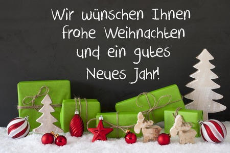 German Text Wir Wuenschen Ihnen Frohe Weihnachten Und Ein Gutes Neues Jahr Means Merry Christmas And Happy New Year. Gifts Decoration Like Tree, Moose Or Red Ball. Black Cement Background With Snow. Stock Photo