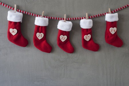 20   24: Nicholas Boots As Advent Calendar Hanging On A Line. Cement Wall As Modern Background. Textile Shoes With Hearts With Numbers 20 Till 24 For Christmas Eve