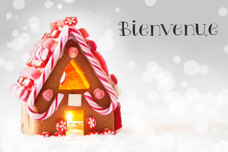 Gingerbread House In Snowy Scenery As Christmas Decoration. Candlelight For Romantic Atmosphere. Silver Background With Bokeh Effect. French Text Joyeux Noel Means Merry Christmas Stock Photo