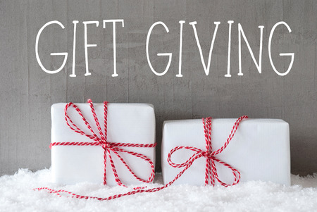 English Text Gift Giving. Two White Christmas Gifts Or Presents On Snow. Cement Wall As Background. Modern And Urban Style. Card For Birthday Or Seasons Greetings.