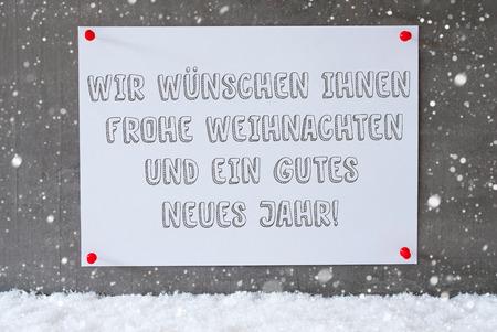 weihnachten: Label With German Text Wir Wuenschen Frohe Weihnachten Und Ein Gutes Neues Jahr Means Merry Christmas And Happy New Year. Urban And Modern Cement Wall As Background On Snow With Snowflakes.